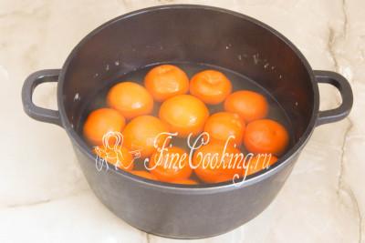 Шаг 5. Ставим посуду с мандаринами на плиту, закрываем крышкой, доводим до кипения, после чего делаем средний огонь