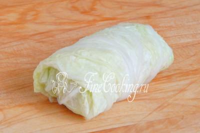 Шаг 11. Подворачивая узкие края, скручиваем лист капусты с начинкой