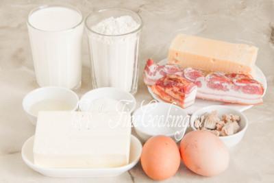Шаг 1. В рецепт этого пасхального кулича входят следующие ингредиенты: пшеничная мука высшего сорта, молоко любой жирности (у меня 2,5%), сливочное масло (жирностью не менее 72%), куриные яйца среднего размера (45-50 граммов каждое), сахарный песок, соль, дрожжи, рафинированное растительное (я использовала подсолнечное) масло, копченая свиная грудинка, а также любой ароматный сыр (типа Российского), который хорошо плавится
