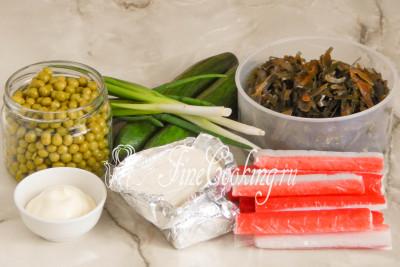 Шаг 1. В рецепт этого простого и вкусного салата входят следующие ингредиенты: маринованная морская капуста, консервированный зеленый горошек, крабовые палочки, свежий огурец, плавленые сырки (типа Дружба), майонез (лучше всего использовать [соус домашнего приготовления](/recipe/majonez-domashnego-prigotovlenija)) и немного зеленого перьевого лука