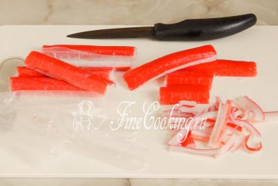 Шаг 3. Охлажденные крабовые палочки (замороженным дать предварительно оттаять в холодильнике) освобождаем от полиэтиленовой оболочки и также нарезаем в длину тонкой соломкой