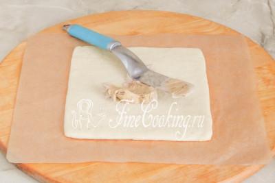 Шаг 26. Первый корж промазываем шоколадным кремом, распределяя ее тонким ровным слоем по всей поверхности