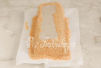 Шаг 38. Обсыпаем бока и немного сверху бисквитной крошкой, плотно прижимая его к крему