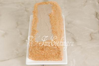 Шаг 39. Аккуратно вытягиваем два отреза пергамента из-под торта, помогая себе лопаткой (придерживаем торт)