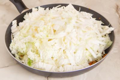 Шаг 5. Добавляем к ним нашинкованную капусту, солим, перчим по вкусу и тушим под крышкой буквально минут 10