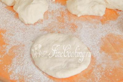 Как формовать пампушки: берем один кусочек теста и на присыпанной мукой поверхности расплющиваем его ладонью, выбивая крупные пузыри воздуха