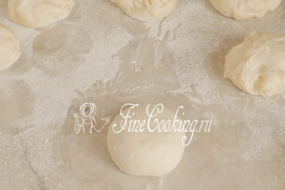 Переворачиваем шарик теста швом вниз и округляем будущие булочки