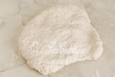 Тыльной стороной ладони разминаем тесто в толстый пласт