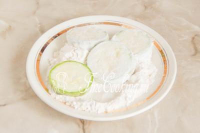 В тарелку просеиваем пшеничную муку и панируем в ней кабачковые кружочки со всех сторон