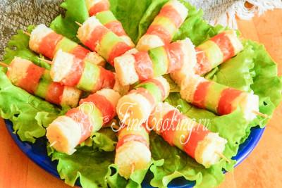 Подаем канапе с соленой рыбой и огурцом на плоском блюде, которое предварительно можно выложить листовым салатом