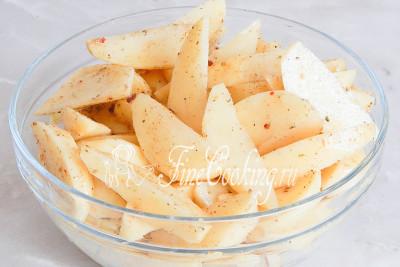 Теперь посыпаем картофельные ломтики любимой приправой и поливаем маслом растительным, чтобы ароматная добавка хорошо прилипла к долькам