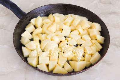 Подливаем еще растительного масла, даем ему как следует прогреться и выкладываем в сковороду кусочки картофеля