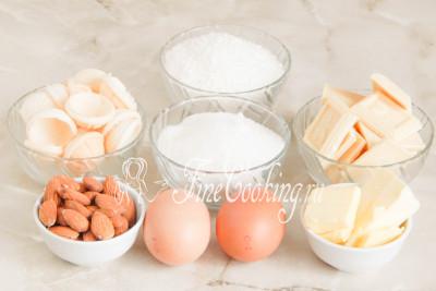Для приготовления домашних конфет Рафаэлло нам понадобятся следующие продукты: белый шоколад, вафельные полусферы (60 штук - это примерно 40 граммов, сахар-песок, кокосовая стружка, яичные белки (у меня на фото целые яйца, но желтки не нужны), сливочное масло и сладкий миндаль (30 штук - это приблизительно 40 граммов)