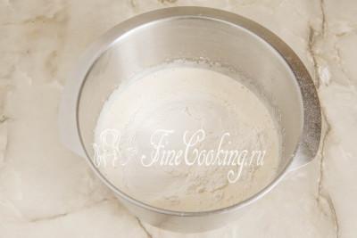 Добавляем в сладкие взбитые яйца 110 миллилитров чуть теплого молока и туда же насыпаем сухую смесь (мука, дрожжи, соль) из шага 3