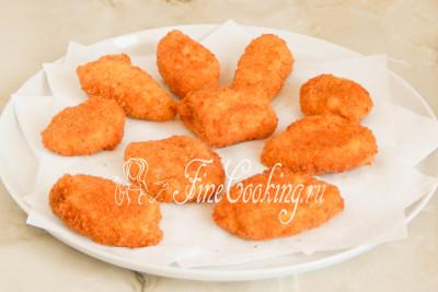 Готовые золотистые куриные наггетсы выкладываем на бумажные салфетки или полотенце, чтобы они впитали в себя излишки масла