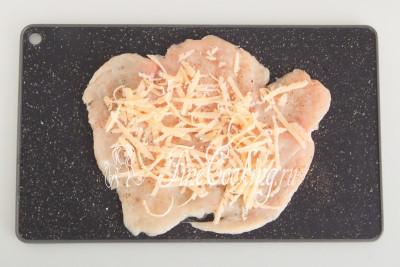 Кладем на куриную грудку часть сыра