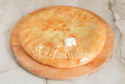 Готовый пирог снимаем с противня и еще горячим смазываем кусочком сливочного масла (за счет этого корочка станет мягкой и нежной)