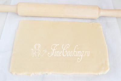 Спустя необходимое время достаем тесто и раскатываем его между двумя листами пергаментной бумаги