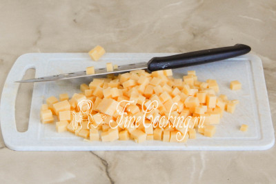 Таким же мелким кубиком нарезаем сыр - 200 граммов