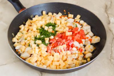 Перекладываем в сковороду к уже успевшей немного остыть начинке сыр, томаты и зелень