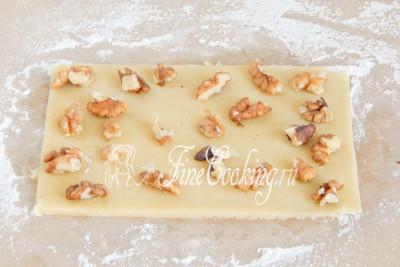 На первый пласт теста раскладываем часть очищенных грецких орешков, которые не нужно сильно измельчать - просто целые кусочки