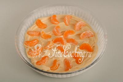 Раскладываем на тесто часть мандариновых долек, слегка вдавливая их в тесто