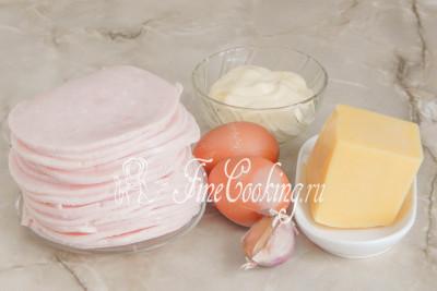 В рецепт этой простой и вкусной закуски входит ветчина, сыр, куриные яйца, майонез и свежий чеснок