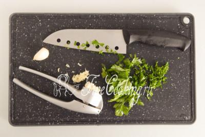 Пучок свежей петрушки мелко рубим ножом, а пару зубчиков чеснока пропускаем через пресс (можно воспользоваться мелкой теркой)