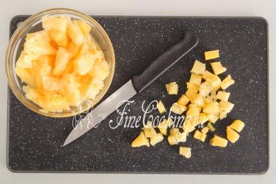 Консервированный ананас (300 граммов - вес без сиропа) откидываем на сито (сироп можно просто выпить), после чего нарезаем фрукты не очень крупным кубиком