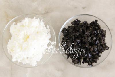 В отдельные миски кладем измельченные маслины и тертый яичный белок - эти два ингредиента нам понадобятся в конце приготовления салата (как декор)