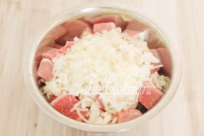 Перекладываем мятый лук вместе с соком к кусочкам свинины