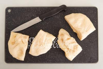 Делим тесто на 4 равные части (разрезаем его ножом) по количеству заготовок