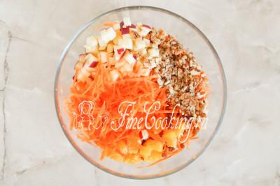 Перекладываем в миску все подготовленные продукты: морковь, яблоки, апельсины (можно нарезать кусочками поменьше), грецкие орешки