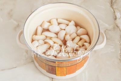 Моем очищенные грибы в холодной проточной воде, кладем в небольшую кастрюльку, заливаем чистой водой и ставим на плиту