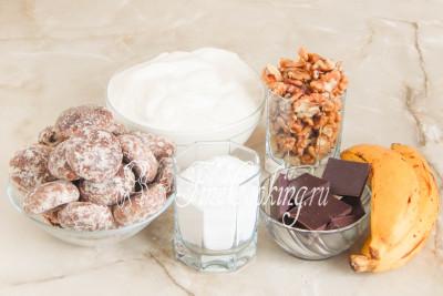 Для приготовления этого домашнего торта без выпечки нам понадобятся следующие ингредиенты: шоколадные пряники, сметана, бананы, очищенные грецкие орехи, сахарная пудра и шоколад