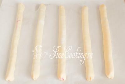 Перекладываем рулетики из теста с начинкой на противень, застеленный бумагой для выпечки, швом вниз