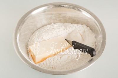 Затем нарезаем прямо в муку 400 граммов сливочного масла, которое должно быть не просто из холодильника, а прямо из морозилки