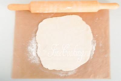Раскатываем с помощью скалки в круг (толщиной не более 2-3 миллиметров), по необходимости припудривая тесто и рабочую поверхность пшеничной мукой