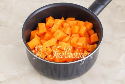 Складываем подготовленную тыквенную мякоть (700 граммов) в подходящую по объему толстостенную кастрюлю или сотейник