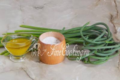 В этот простой и оригинальны рецепт заготовок на зиму входят стрелки чеснока, оливковое масло (можно заменить любым другим растительным) и соль