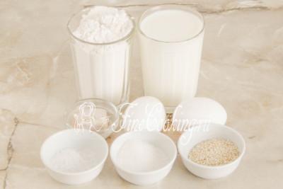 Для начала подготовим все необходимые продукты для приготовления дрожжевых булочек: пшеничную муку высшего сорта, молоко любой жирности (у меня 2,8%), куриные яйца среднего размера (45-50 граммов каждое), сахарный песок, соль, семена кунжута, а также дрожжи