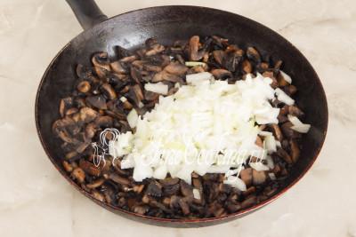 Когда грибы хорошо поджарятся, добавляем измельченный лук, делаем средний огонь и продолжаем готовить шампиньоны до мягкости и легкого румяного цвета лука