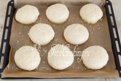 Когда заготовки заметно увеличатся в объеме, смазываем их смесью яичного желтка и молока из шага 6 - благодаря этому поверхность булочек будет румяной и блестящей