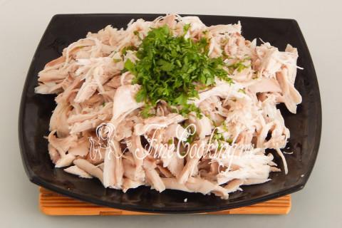 Несколько веточек свежей петрушки мелко рубим ножом и добавляем к курице